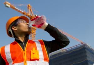 worker man  as he drinks from a plastic water bottle