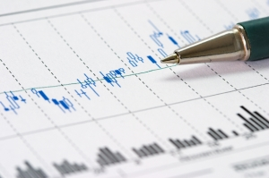 Closeup of ballpoint pen over a candlesticks stock chart (very shallow dof; focus on pen tip).